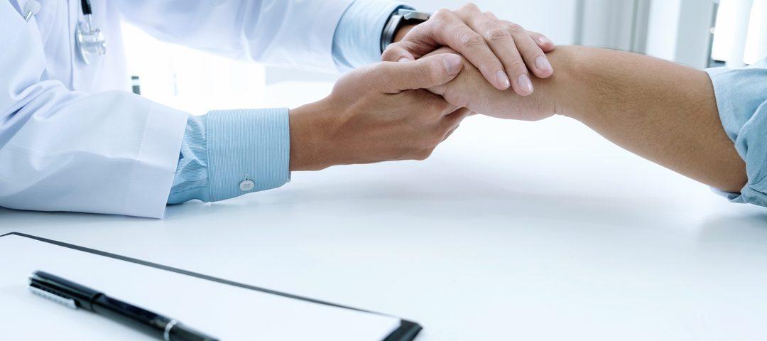 Diagnóstico precoce: médico aperta mão de paciente em gesto de apoio.