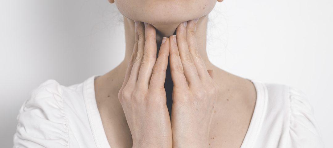 Mulher massageando garganta dolorida com as mãos