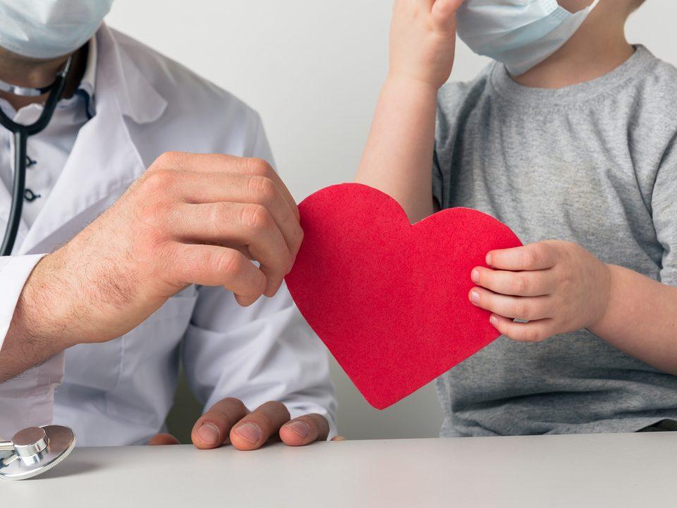 criança e doutor segurando coração fazendo alusão ao atendimento humanizado