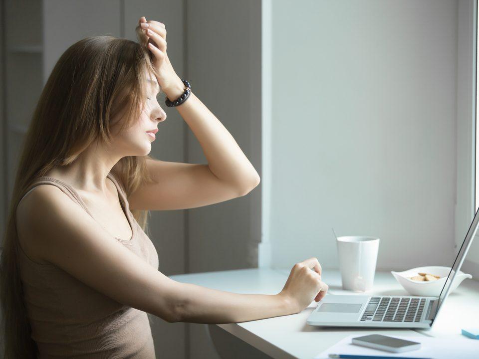 mulher na frente de notebook com mão na cabeça expressando dor de cefaleia