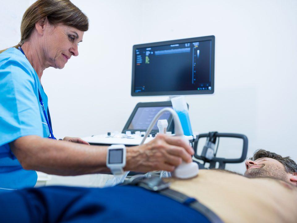 Exame ultrassonográfico: homem realizando o exame ultrassonográfico com médica